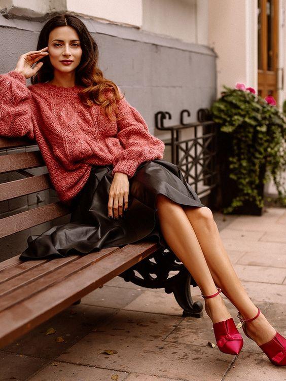 Розовый свитер крупной вязки в сочетании с черной свободной кожаной юбкой-миди и ярко-розовыми туфлями, украшенными маленьким бантом.