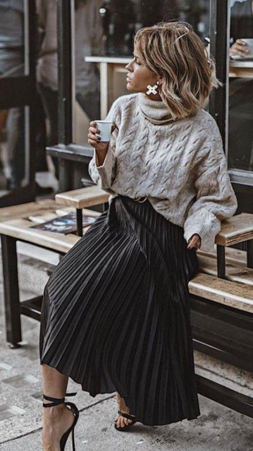 Серый свитер крупной вязки с ажурным узором в сочетании с черной юбкой-плиссе длины миди и босоножками на шпильке.