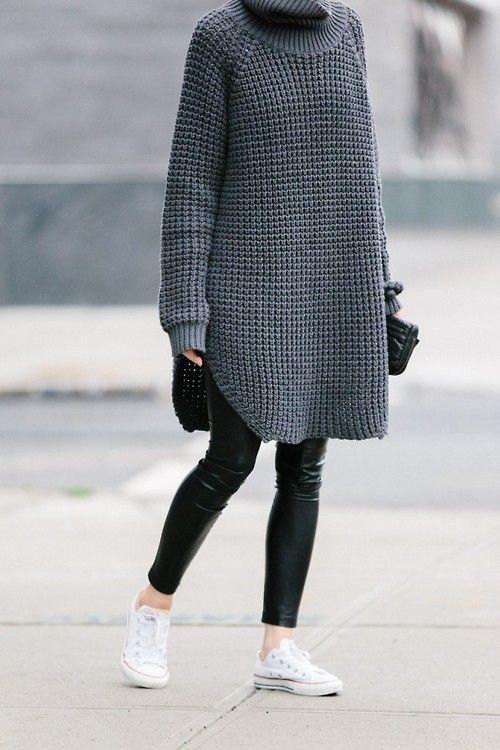 На девушке серый удлиненный свитер крупной вязки с разрезами по бокам, черные кожаные леггинсы, белые кеды и сумка-клатч.