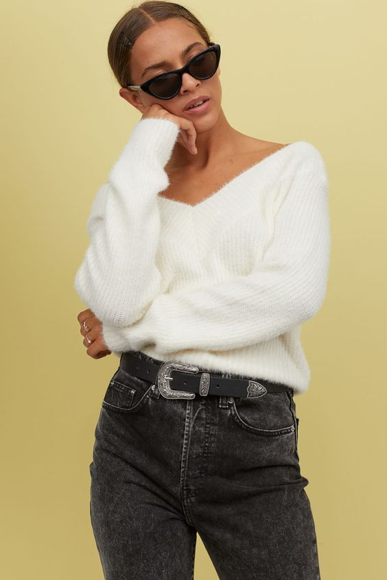 На девушке белый свитер с V-образным воротником, черные прямые джинсы, узкие очки.