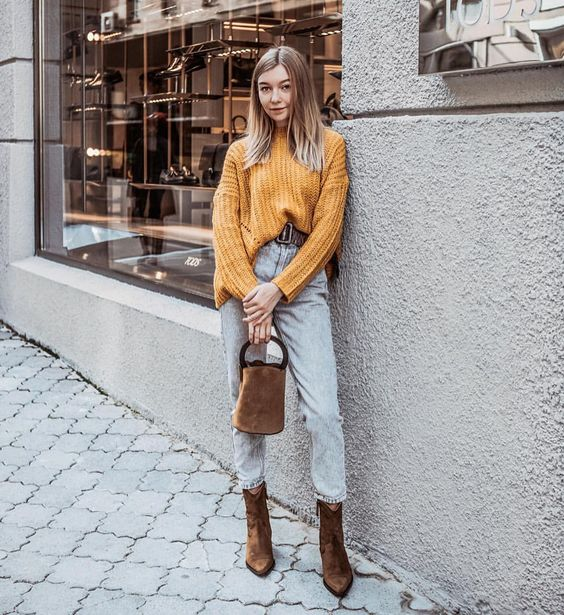 На девушке свитер крупной вязки горчичного цвета, светло-голубые джинсы прямого кроя, коричневые замшевые ботинки на каблуке и такого же цвета сумка.