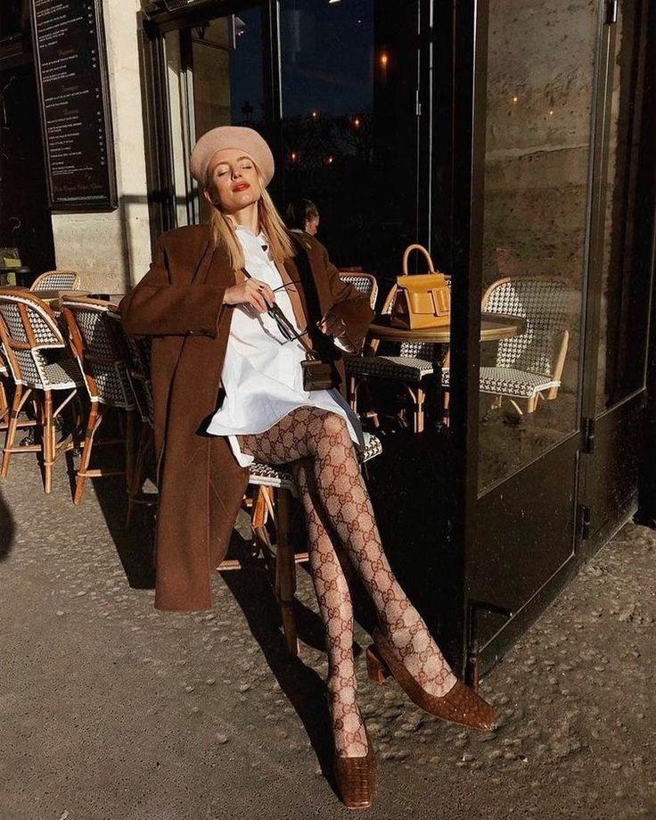 На девушке бежевый фетровый берет, белая плотная рубашка-платье, светло-коричневые колготки с узором, кожаные коричневые мюли с квадратным носом, коричневое пальто прямого кроя.