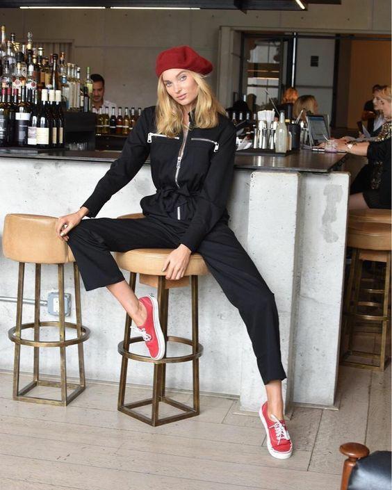 На девушке красный фетровый берет, надетый набок, черный спортивный комбинезон, красные кеды на белой подошве.