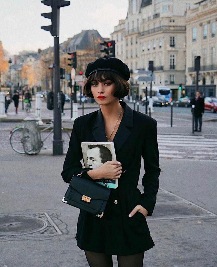 На девушке черный фетровый берет с кожаной резинкой, черный классический пиджак с поясом и золотыми пуговицами, тонкие колготки и кожаная квадратная сумка.