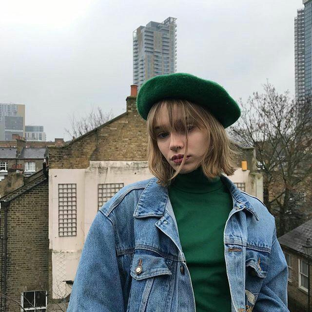 Зелёный берет в сочетании с голубой джинсовой курткой и зелёной облегающей водолазкой.