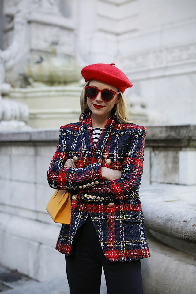 На девушке красный фетровый берет, красно-синий твидовый пиджак прямого кроя с принтом тартан и золотыми металлическими пуговицами, прямые черные брюки, полосатая кофта, желтая поясная сумка и очки.