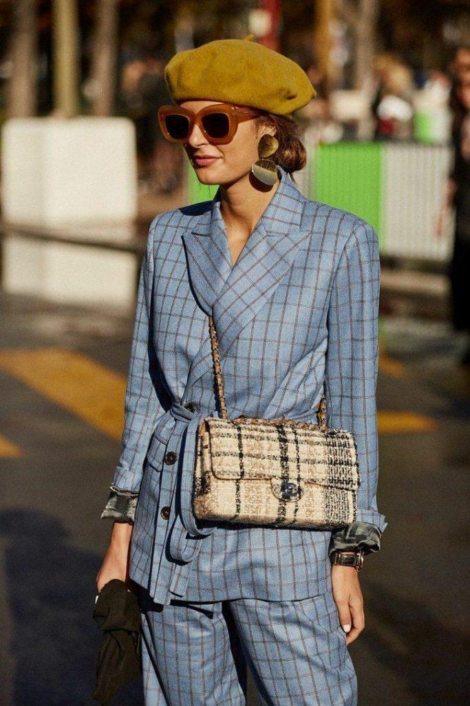 На девушке горчичный фетровый берет, голубой клетчатый костюм: свободные брюки и пиджак оверсайз с поясом, твидовая бежевая поясная сумка, объемные серьги и очки.