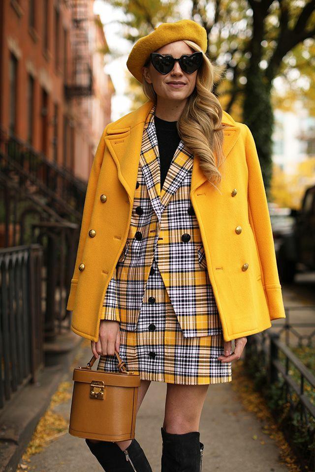 На девушке горчичный фетровый берет, черная водолазка, клетчатый желтый костюм в клетку Burberry: прямая юбка мини, пиджак, желтый удлиненный жакет, черные очки в форме сердца, замшевые черные ботфорты, коричневая сумка.