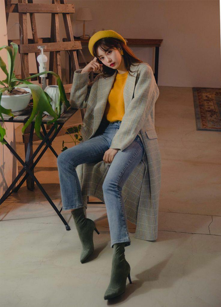 На девушке горчичный берет, желтый свитер, синие прямые джинсы, темно-зеленые ботильоны-носки с заостренным носом, серое клетчатое пальто длины миди.