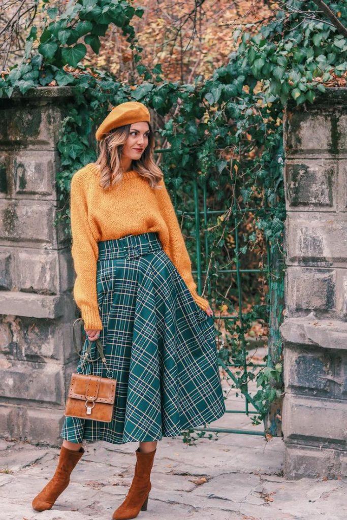Горчичный фетровый берет в сочетании с такого же цвета свитером, зелёной клетчатой юбкой-клеш длины миди, замшевыми коричневыми ботинками на толстом каблуке и кожано коричневой сумкой.