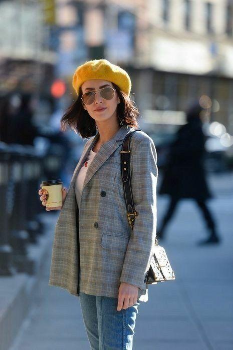 На девушке желтый фетровый берет, белая футболка, серый клетчатый пиджак прямого кроя, голубые джинсы и поясная сумка.