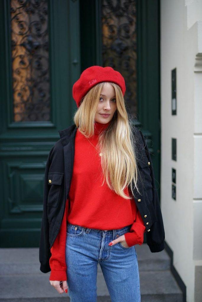 На девушке красный фетровый берет, красный свободный свитер с воротом, тонкая золотая цепочка,  синие прямые джинсы со средней талией, черная куртка с золотыми пуговицами.