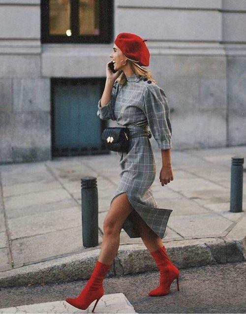 На девушке красный берет, серое клетчатое платье длины миди, с широкими рукавами, поясом и разрезом сбоку, красные ботильоны-носки на высоком тонком каблуке и с заостренным носом, черная поясная сумка.
