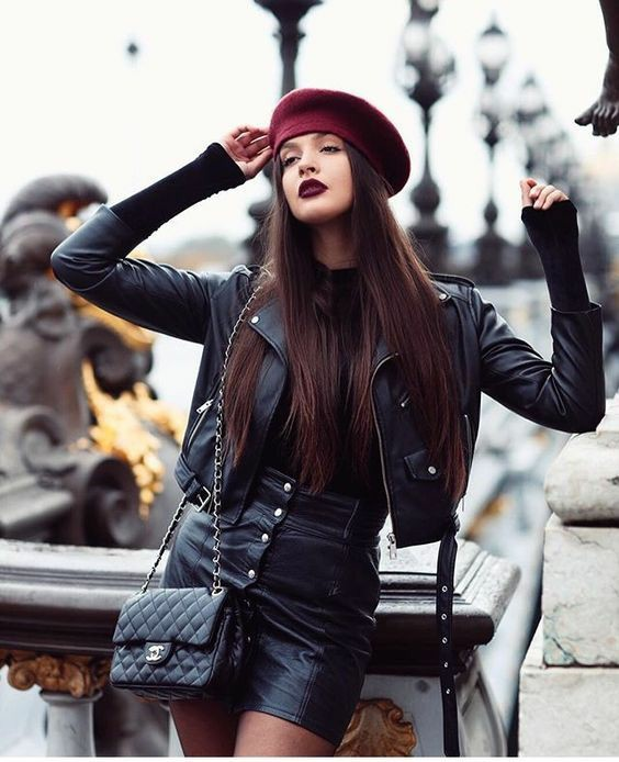 Бордовый фетровый берет, надетый набок в сочетании с укороченной черной кожаной курткой, облегающей кожаной юбкой длины мини, тонкими черными колготками, поясной кожаной сумкой.