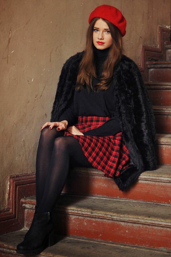 На девушке красный берет, черная водолазка с длинным воротом, клетчатая красная юбка-солнце длины мини, черные колготки, короткая шуба и черные ботинки на плоском ходу.