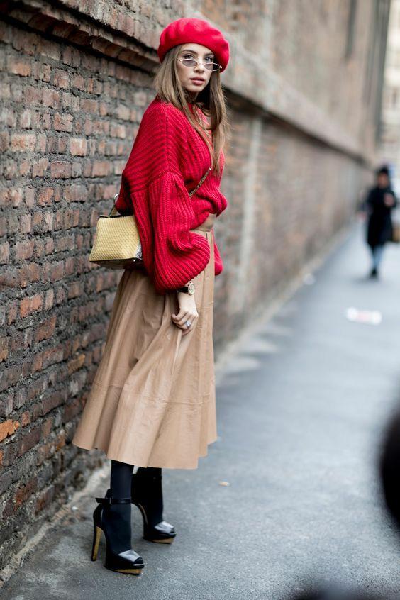 На девушке красный кожаный берет, объемный красный свитер со свободными рукавами, кожаная юбка плиссе длины миди, плотные черные колготки, черные туфли на высоком каблуке и с открытым носом, круглые узкие очки и желтая сумка.
