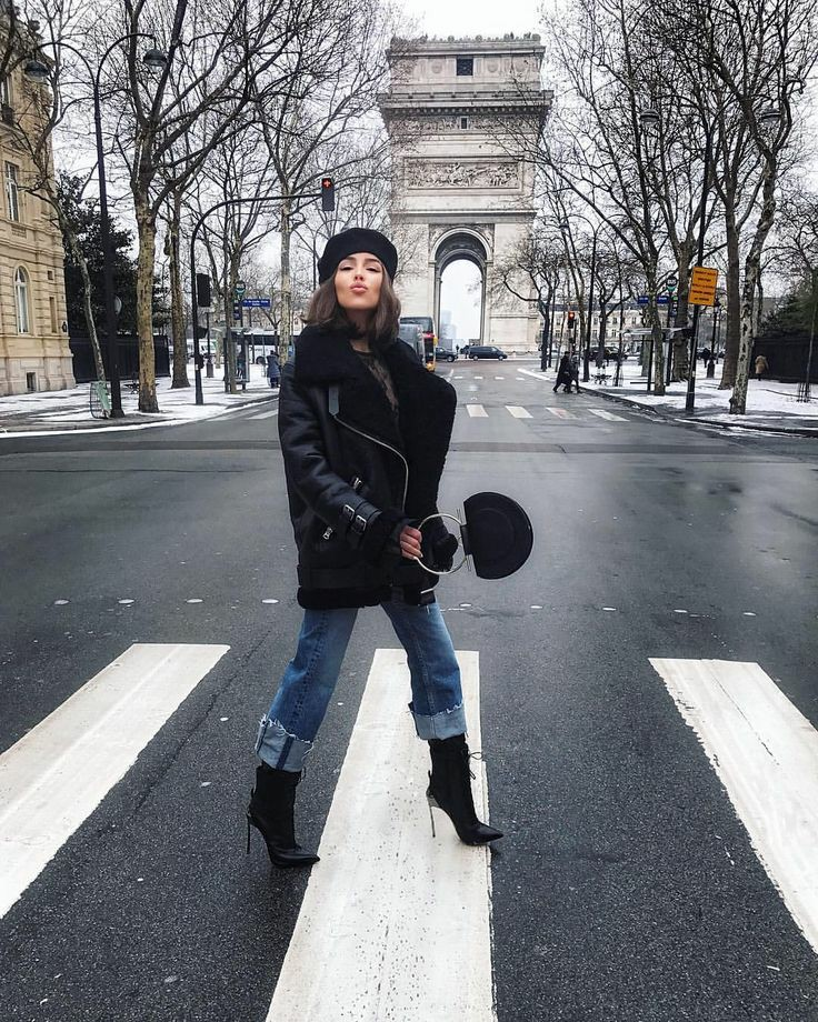 Черный фетровый берет в сочетании с черной кожаной дубленкой оверсайз, синими свободными джинсами с высокими отворотами, кожаными черными ботинками на шпильке и с заостренным носом.