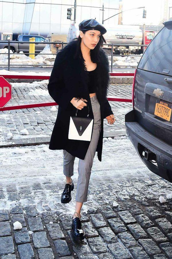 На девушке черный кожаный берет, надетый набок, черный топ, серые классические брюки длиной ⅞, черная шуба с искусственным мехом длиной до середины колена, лаковые черные ботинки на шнуровке, белая квадратная сумка.
