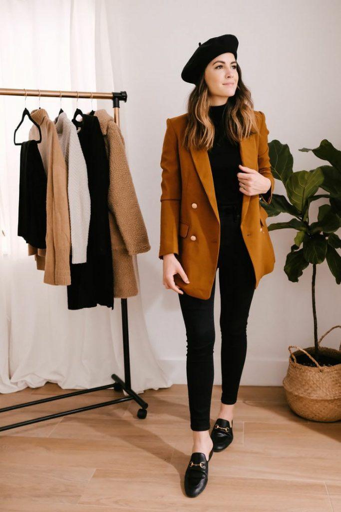 Аутфит состоит из черного фетрового берета, черной водолазки, коричневого удлиненного пиджака прямого кроя, черных скинни.