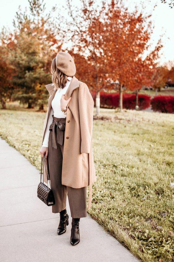 """На девушке бежевый берет, такого же цвета пальто прямого кроя, белая водолазка с воротом, коричневые кюлоты """"гусиная лапка""""с  поясом, темно-коричневые ботинки с заостренным носом, кожаная сумка."""