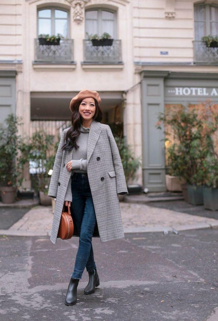 Бежевый фетровый берет в сочетании с серой кашемировой водолазкой, серым клетчатым пальто прямого кроя, темно-синими облегающими джинсами, черными кожаными ботинками на толстом каблуке, круглой коричневой сумкой.