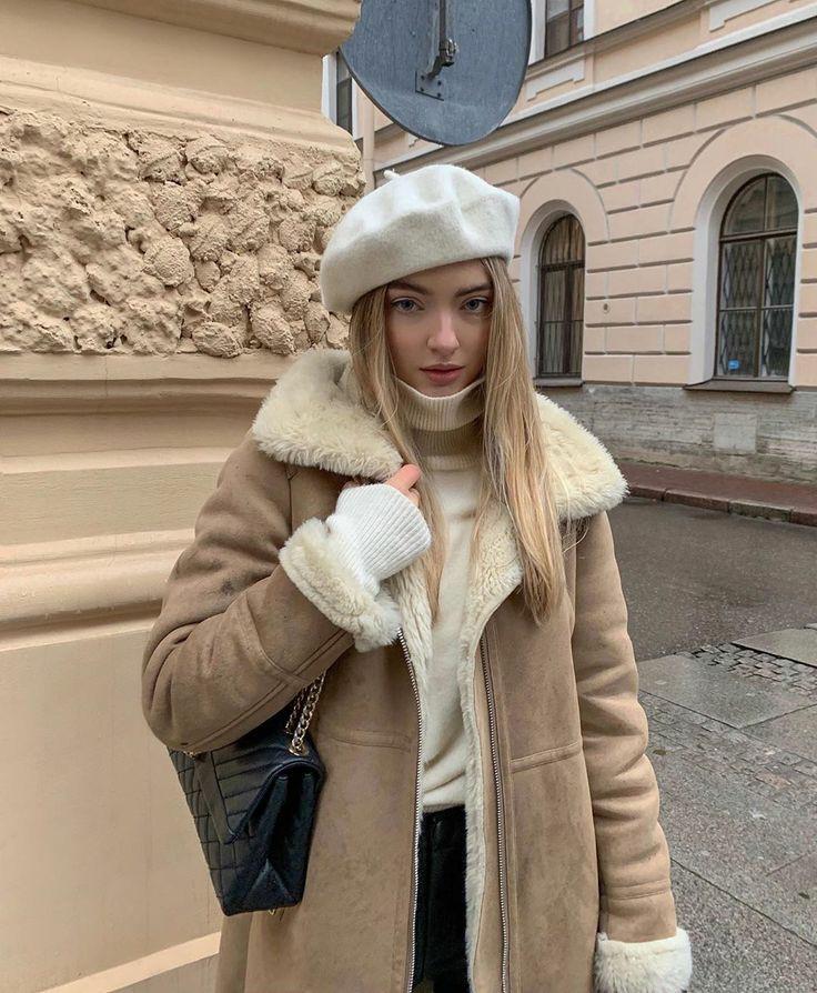 На девушке белый шерстяной берет, молочная водолазка с высоким воротом, темно-бежевая дубленка с белым мехом, джинсы и кожаная черная сумка.