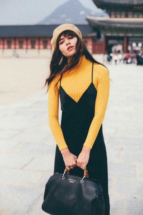 На девушке бежевый фетровый берет, желтая водолазка в рубчик с воротом, черное платье миди на тонких бретелях и с глубоким V-образным вырезом, большая черная сумка.