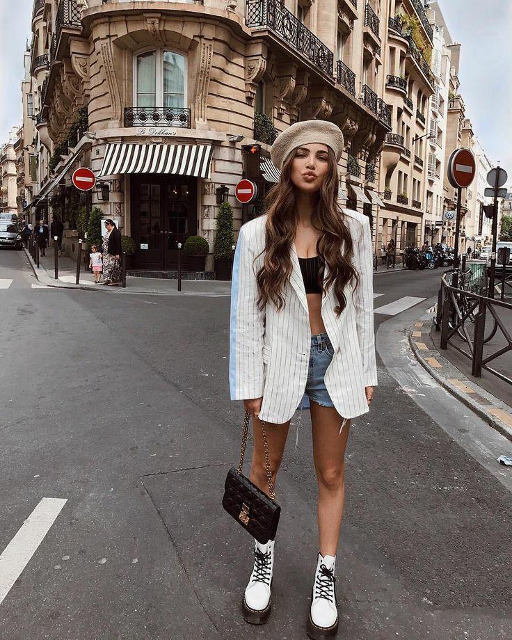 Бежевый объемный берет в сочетании с коротким черным топом, белым пиджаком в тонкую черную полоску, голубыми синими джинсами, белыми кожаными ботинками на толстой подошве и шнуровке.