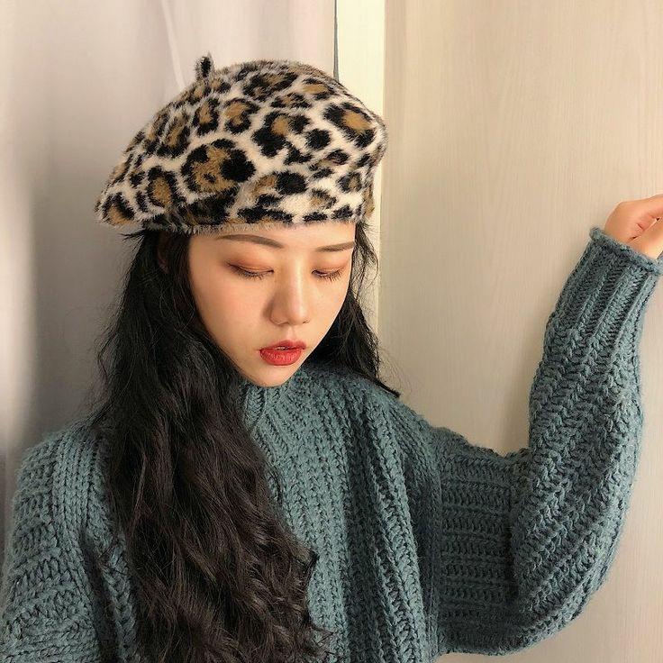 На девушке меховой коричневый леопардовый берет, надетый набок, темно-голубой объемный свитер крупной вязки.