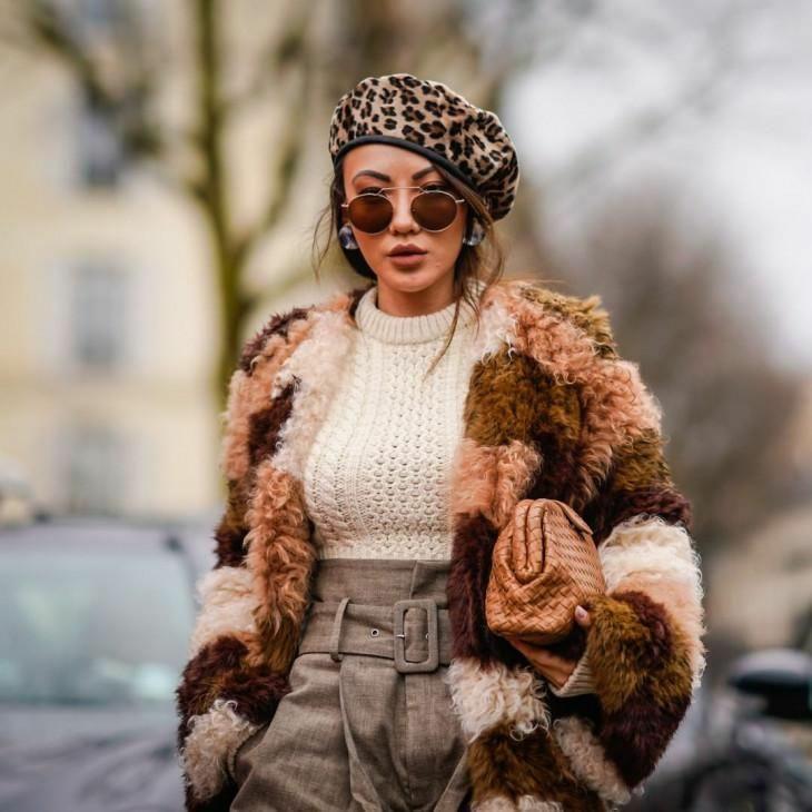 На девушке светло-коричневый леопардовый берет, вязаный молочный свитер крупной вязки, брюки-бананы, коричневая шуба с кудрявым ворсом, объемный коричневый клатч.