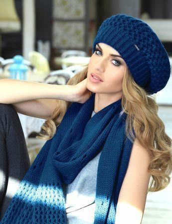 На девушке синий вязаный берет с ажурной вязкой, вязаный синий шарф, серая свободная майка.