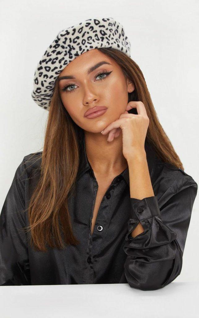На девушке светлый леопардовый берет и черная атласная блузка.