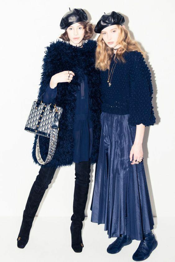 Первая девушка надела кожаный синий берет, синее шифоновое платье, кудрявую синюю жилетку и замшевые высокие сапоги. На второй девушке синий кожаный берет, синий свитер крупной вязки, кожаная юбка плиссе длины макси и кожаные синие ботинки.