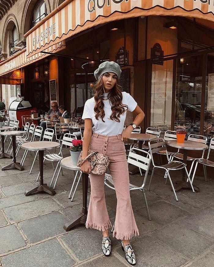 На девушке серый фетровый берет, белая базовая футболка, вельветовые нежно-розовые брюки-кюлоты, кожаные мюли в анималистическом принте и сумка-клатч.