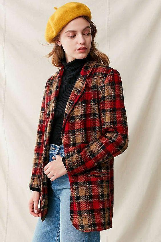 На девушке горчичный фетровый берет, черная облегающая водолазка, голубые прямые джинсы со средней талией, красно-коричневый клетчатый пиджак прямого кроя.
