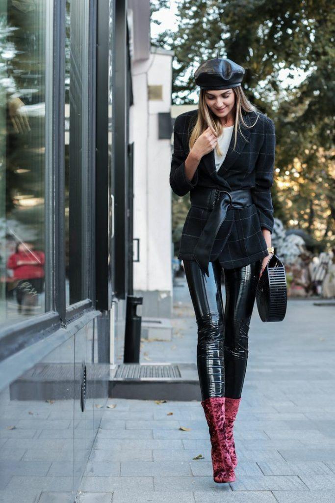 На девушке кожаный черный берет, белая футболка, кожаные облегающие брюки, черный клетчатый пиджак с широким кожаным поясом, бордовые ботильоны-носки на каблуке, сумка круглой формы.