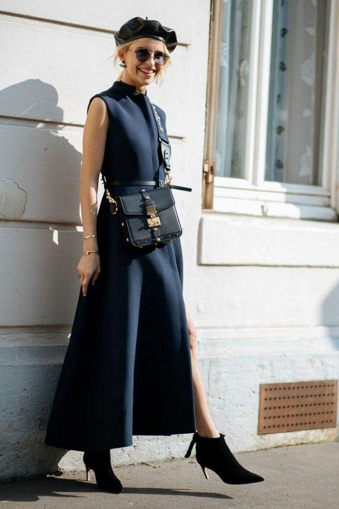 На девушке кожаный черный берет, темно-синее платье без рукавов с тонким кожаным ремнем, пышной юбкой длины макси, замшевые ботинки на тонком коротком каблуке и с заостренным носом, кожаная черная поясная сумка.