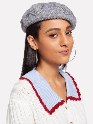 На девушке серый вязаный берет, круглые большие серьги, белая трикотажная кофта с голубым воротником.