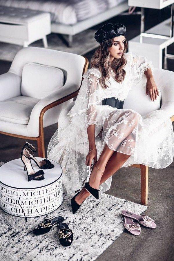 На девушке кожаный черный берет, белое шифоновое платье с кружевными вставками и рюшами, длины миди, с черным широким поясом, замшевые черные лодочки.
