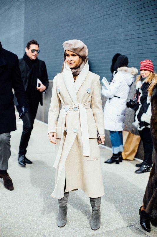 """На девушке бежевый фетровый берет, такого же цвета шарф, бежевое свободное пальто длины миди с поясом и объемными пуговицами, замшевыми серыми ботфортами """"гармошка""""."""