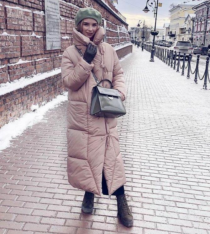 На девушке светло-зеленый фетровый берет, нежно-розовая дутая куртка длины миди, кожаные ботинки на толстой подошве и шнуровке, лаковая большая поясная сумка и кожаные перчатки.