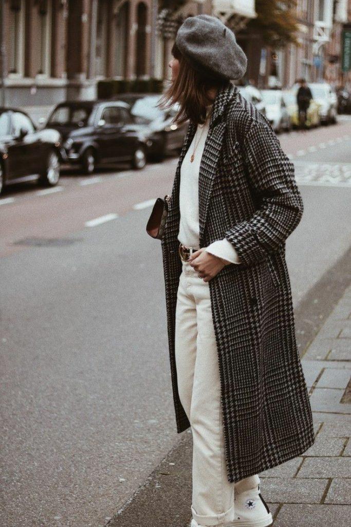 На девушке серый фетровый берет, белый свитер, белые прямые джинсы со средней талией, белые кеды и серое клетчатое пальто прямого кроя длины миди.
