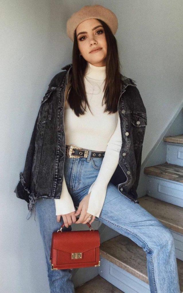 На девушке бежевый фетровый берет, черная джинсовая куртка, молочный свитер с воротом, синие прямые джинсы со средней талией, красная сумка квадратной формы.