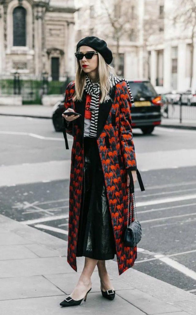 На девушке черный фетровый берет, черная водолазка, кожаная черная юбка плиссе длины миди, красное пальто прямого кроя длины макси, черные туфли на низком каблуке, полосатый белый шарф, поясная кожаная сумка.