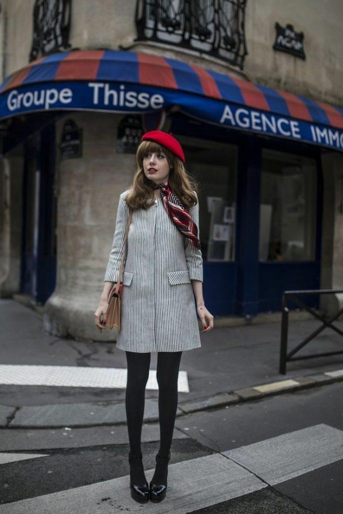 На девушке красный берет, надетый набок, белое пальто трапеция, плотные черные колготки, лаковые черные туфли на платформе и каблуке, шарф и коричневая поясная сумка.