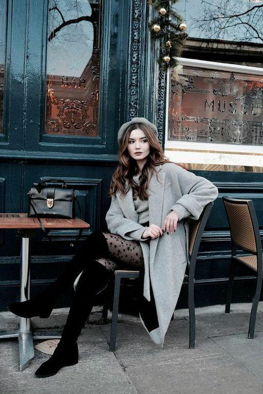 На девушке серый фетровый берет, серое кашемировое пальто прямого кроя длины миди, серое шерстяное платье, тонкие черные колготки с узором, замшевые ботфорты выше колена.