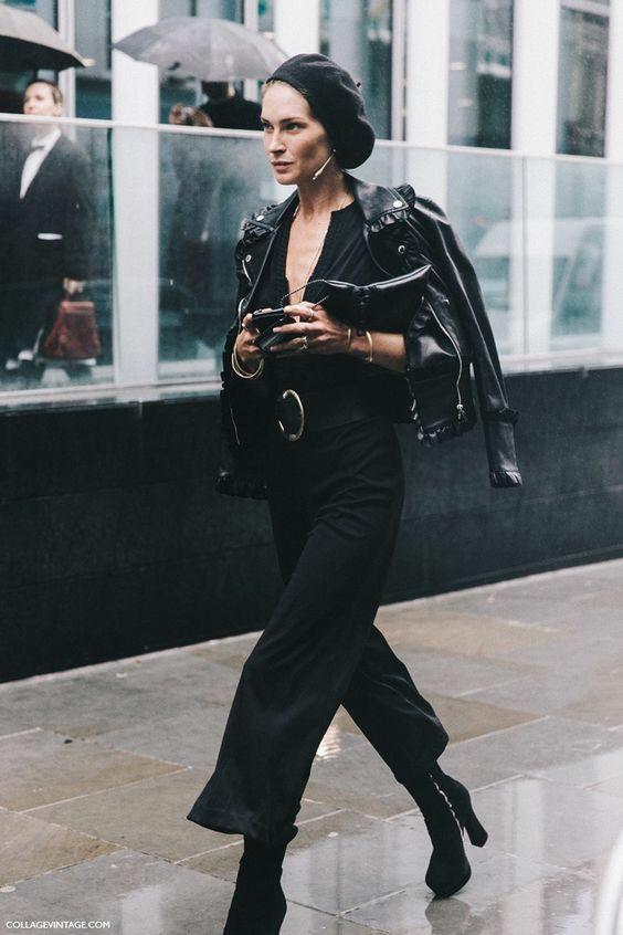 На девушке черный фетровый берет, черная блуза с глубоким вырезом, черные брюки-клеш, черная кожаная куртка и замшевые черные ботинки на платформе и каблуке.