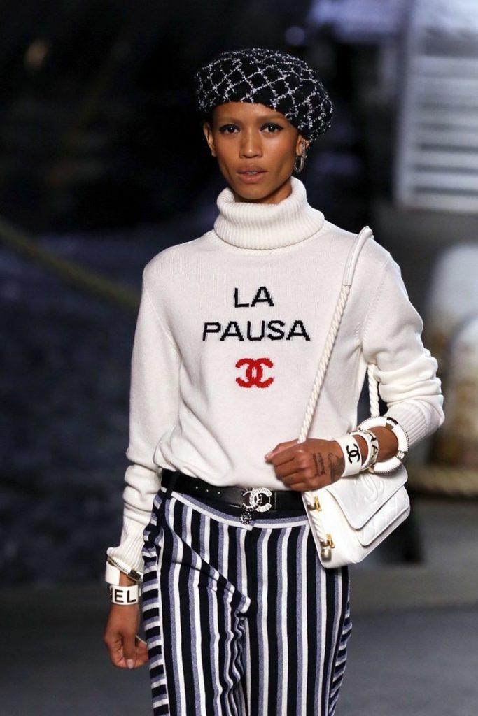 На девушке твидовый черный берет с геометрическим узором, белый свитер с объемным горлом, полосатые свободные брюки. Образ дополняют аксессуары: белые браслеты и кожаная поясная сумка.