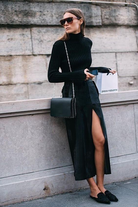 На девушке черная облегающая водолазка с горлом, черная прямая юбка длины миди и с разрезом спереди, замшевые мюли на плоском ходу и с открытой пяткой, поясная черная сумка-кроссбоди, очки.