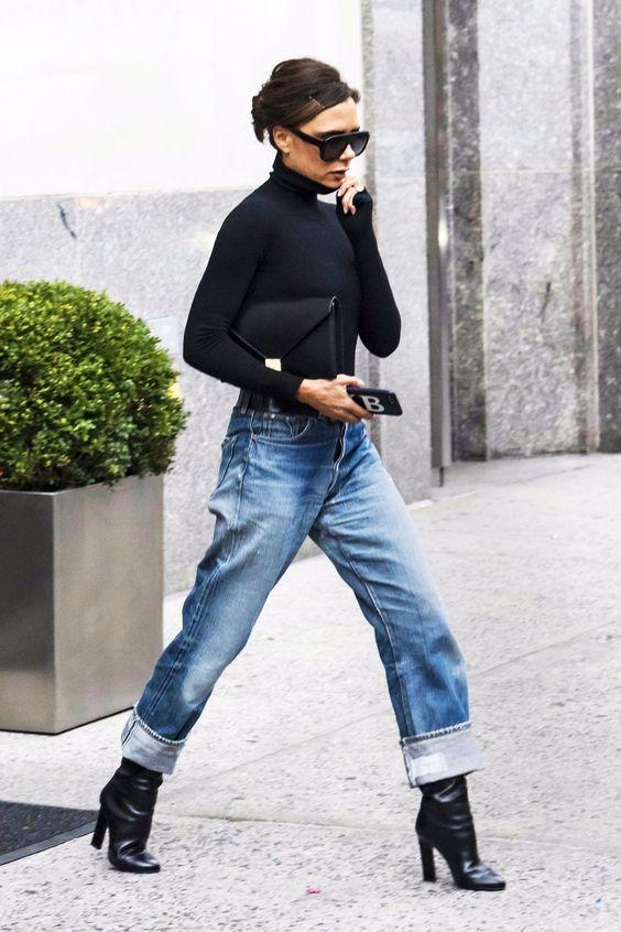 Черная облегающая водолазка в сочетании с прямыми джинсами-варенками, черными ботинками на высоком толстом каблуке, очками и черным клатчем.